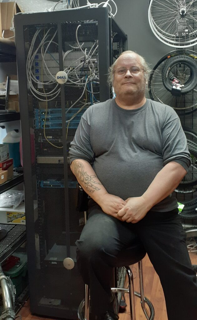 Ron at work, seated and smiling. Behind him are wires for electronics, with additional storage behind