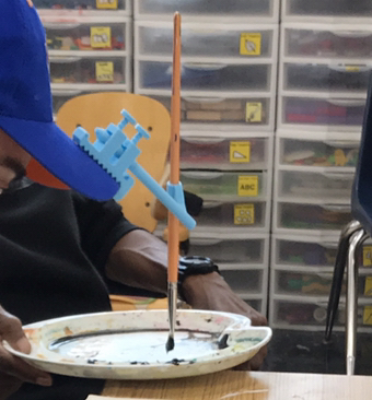 a person uses an adapted head pointer attached to their baseball cap to dip a paintbrush in paint