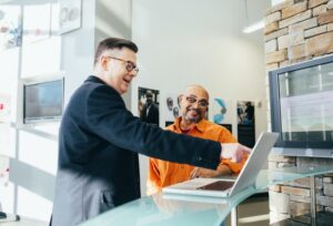 a man points at a computer, while another man looks on