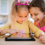 two children are using a tablet, one is scrolling, while the other is watching with a smile