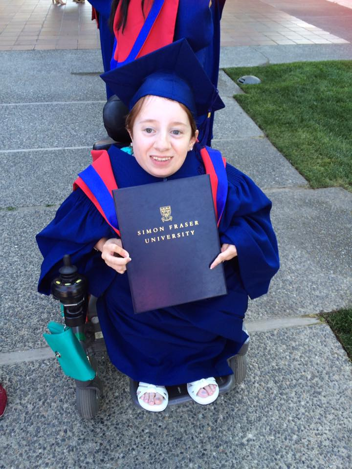 Amelia in her graduation gown, holding her degree.